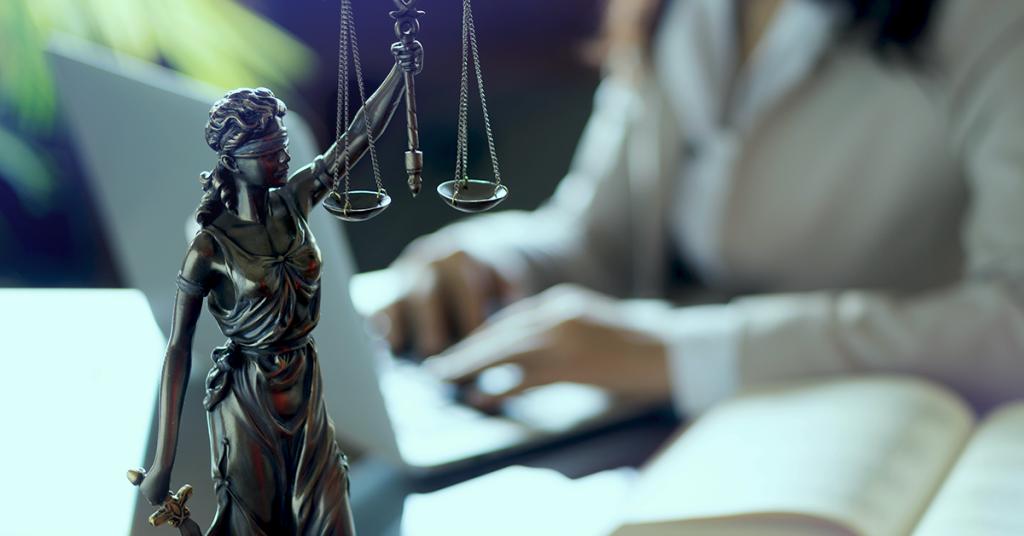Uma estátua que representa a justiça e, desfocado ao fundo, um advogado digitando em um notebook. Imagem representa passos inciais para quem quer abrir um escritório de advocacia.