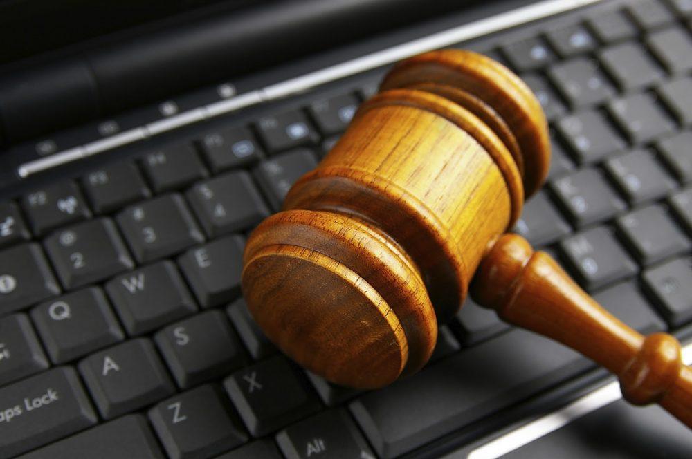 Martelo de juiz repousado sobre um teclado de computador. Representa bem a discussão sobre publicidade da advocacia.