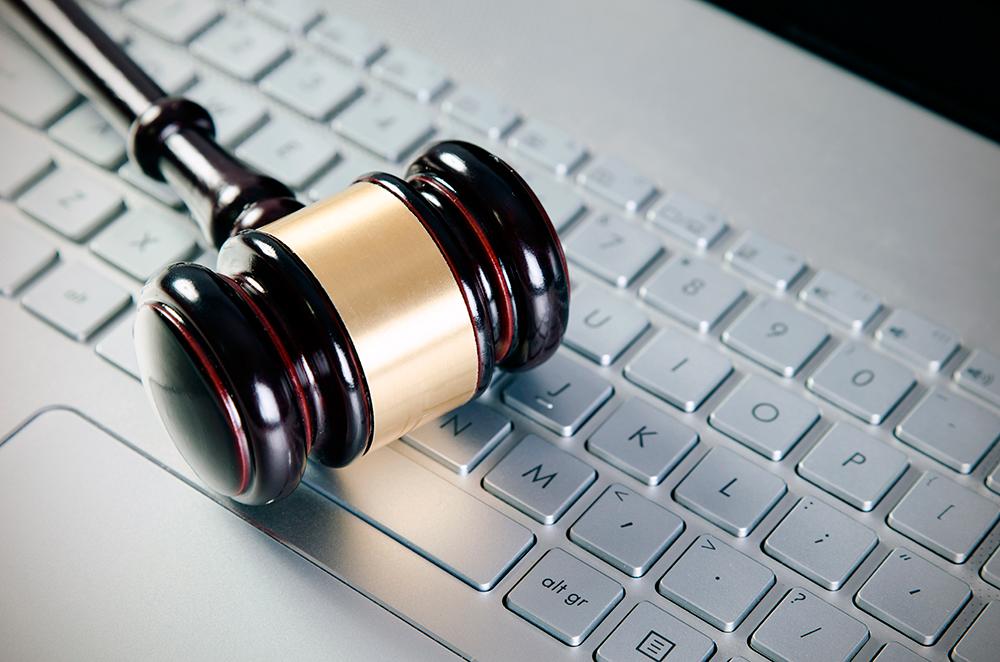 Martelo de juíz sobre o teclado de um notebook, mostrando a evolução do direito online e como a internet tem agilizado a advocacia.