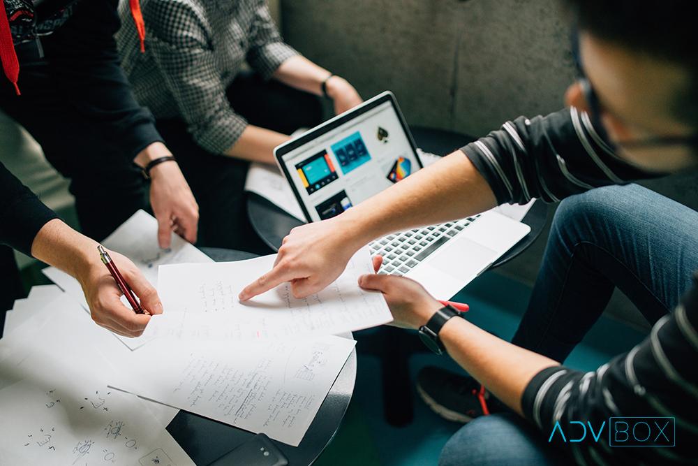 A imagem mostra uma equipe de um escritório trabalhando com papéis e um notebook à mesa. Veja aqui 7 motivos para criar um Blog Jurídico.