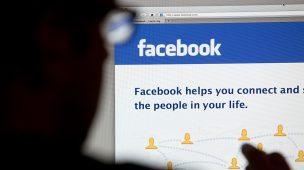 Silhueta de um homem de óculos olhando para a tela de um compotador onde está aberta uma página do Facebook. Imagem serve para ilustrar a possibulidade de recorrer a redes sociais para realizar a revisão do auxílio doença e de outros benefícios.