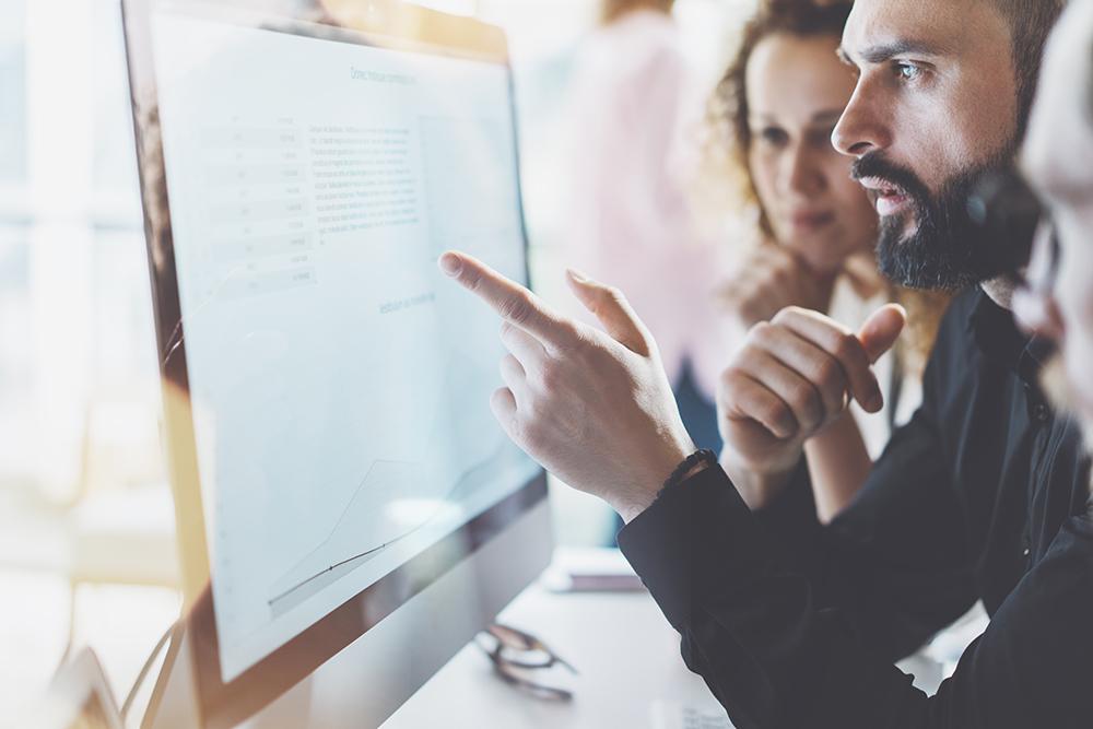 Alguns advogados reunidos apontando para a tela de um computador, representando a gestão de escritório de advocacia