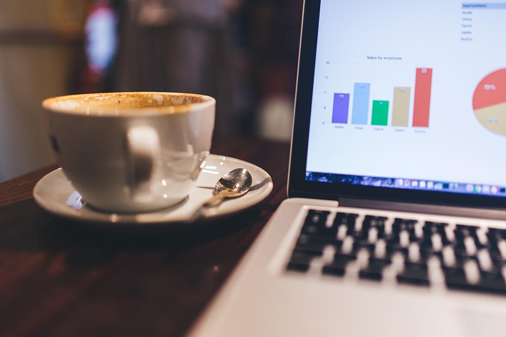 Xícara de café em uma mesa ao lado de um notebook mostrando gráficos de acessos geridos por SEO. Foto representa a importância do marketing jurídico para o sucesso de site de advogados.