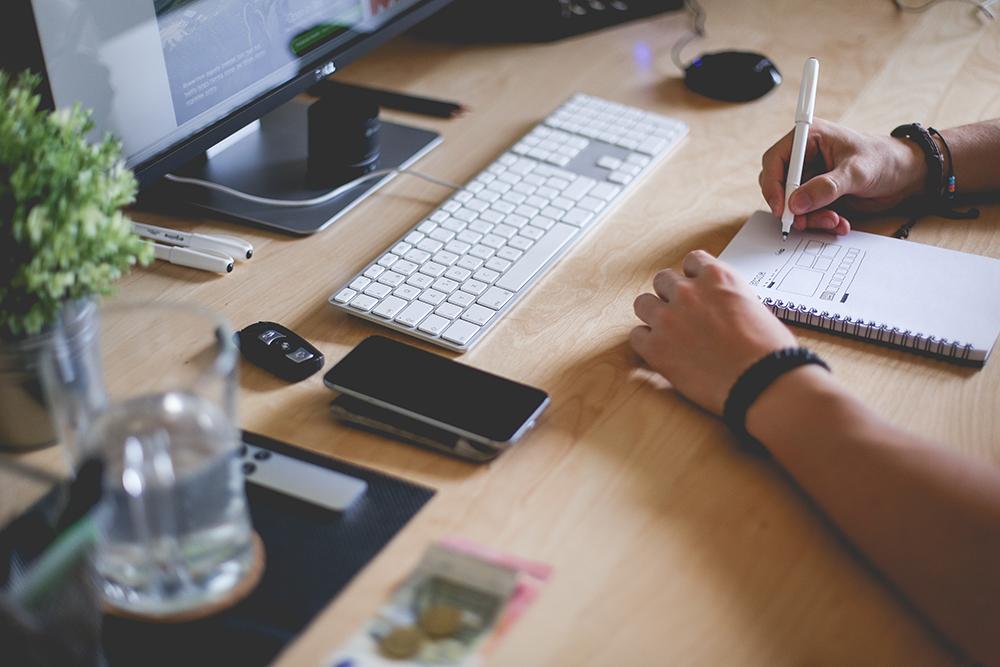 Uma mesa com computador, com um celular ao lado do teclado, onde há também alguém escrevendo em um bloco de notas, representando o planejamento estratégico necessário para quem trabalha com marketing de conteúdo