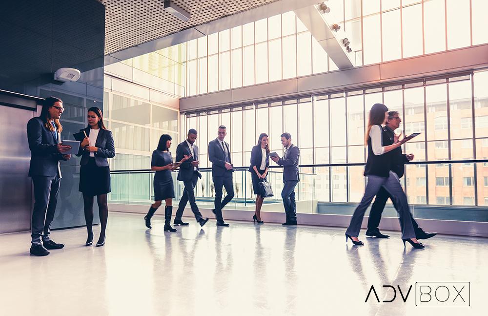 A imagem mostra advogados andando em um grande escritório. Leia aqui sobre softwares de gestão e marketing jurídico em escritórios.