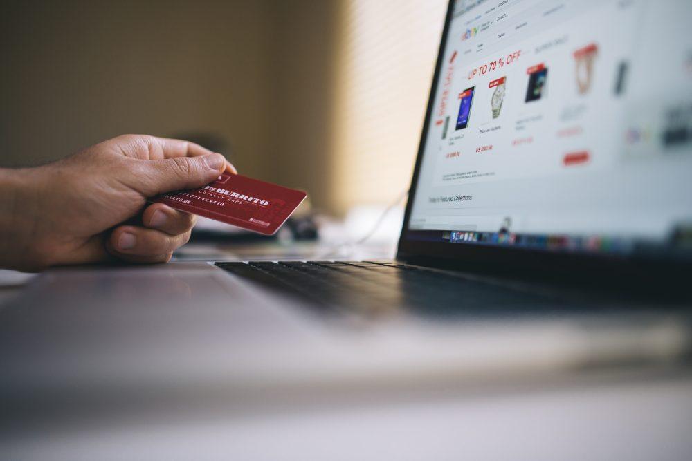 A imagem mostra uma pessoa com seu cartão bancário prestes a realizar uma compra na internet. Nesse momento, é sempre bom ter em mente as leis do e-commerce. Assim se evita possíveis problemas no futuro.