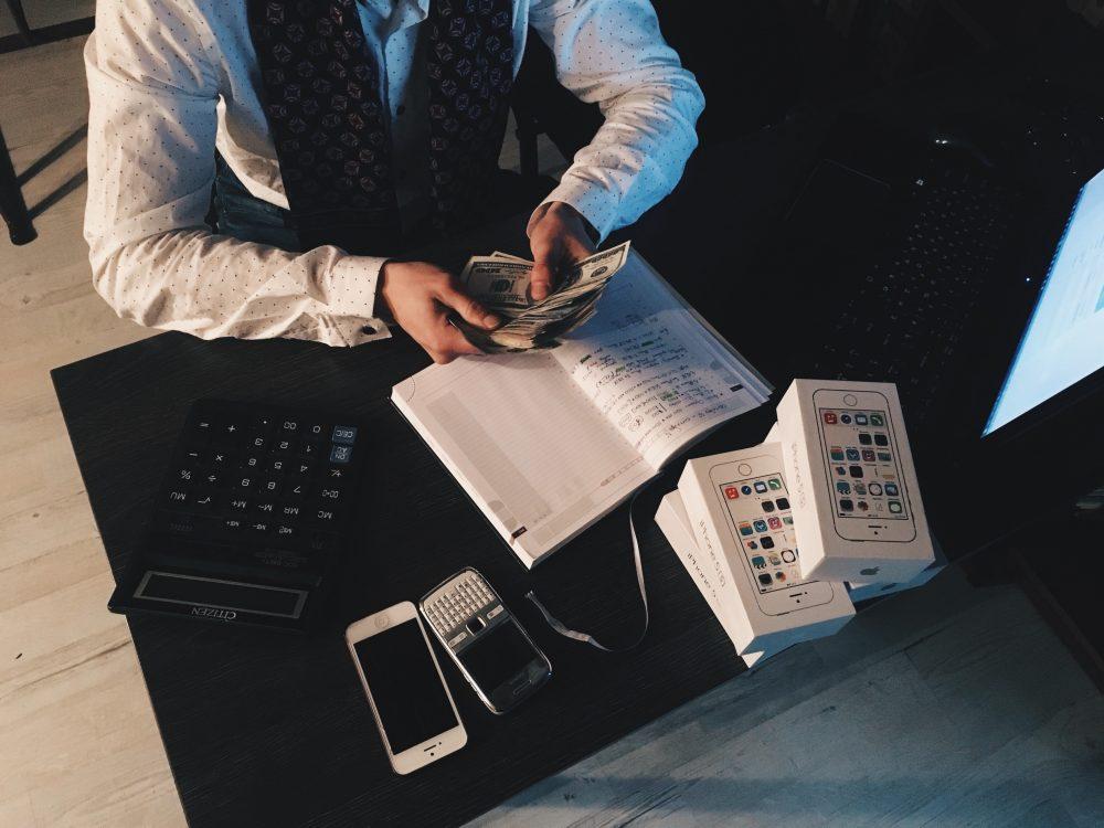 Advogaado com diversos aparelhos eletrônicos digitais sobre a mesa, representando o escritório online