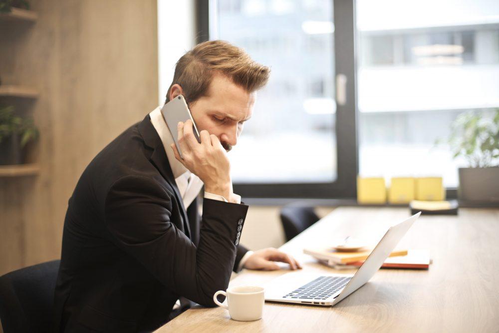 Um homem com telefone no ouvido e digitando em um notebook, demonstrando a facilidade dos dias atuais para o Atendimento de clientes de fora do Brasil