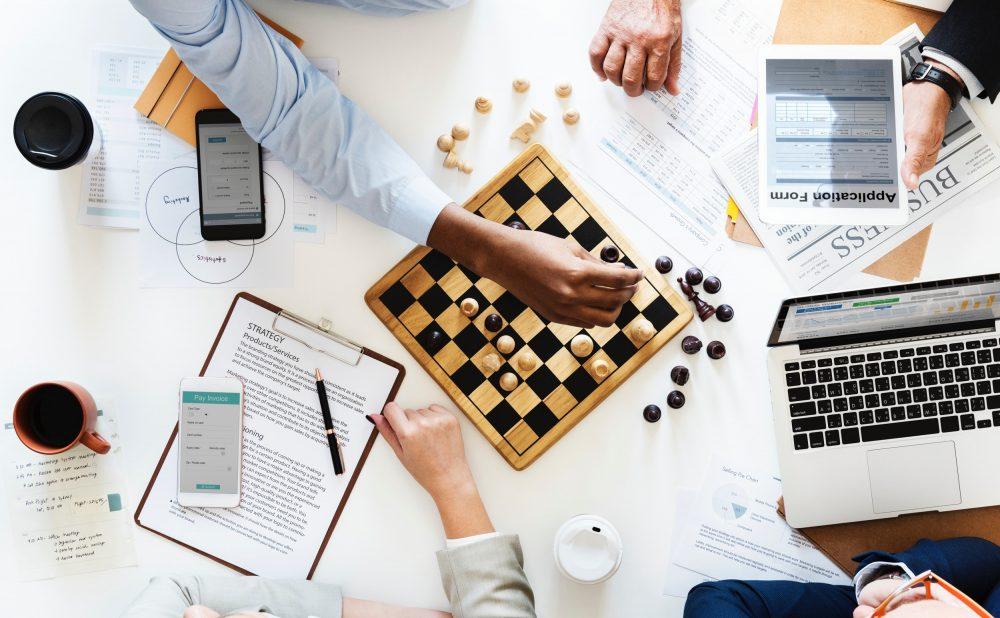 Algumas pessoas jogando xarex sobre uma mesa com material de escritório, representando estratégias para conquistar oportunidades de negócios