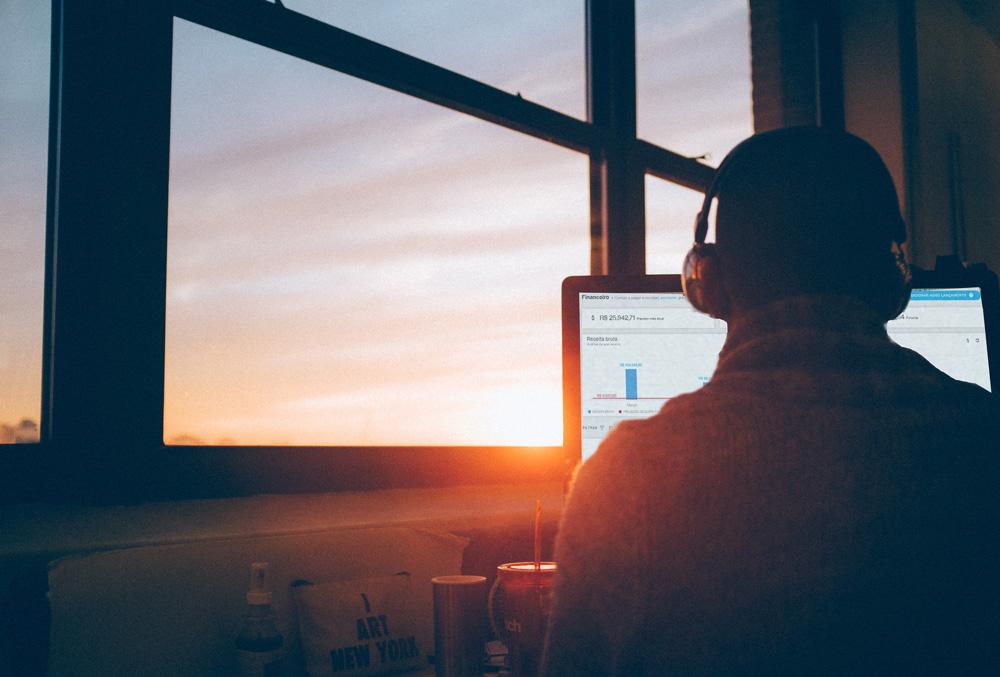 Um homem com a Advbox aberta na tela do computador em frente a uma janela com o sol se pondo. Os gráficos na tela demonstram os custos fixos do escritório