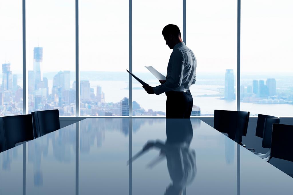 Um homem em frente a uma janela analisando documentos, representando como planejar investimentos em escritório