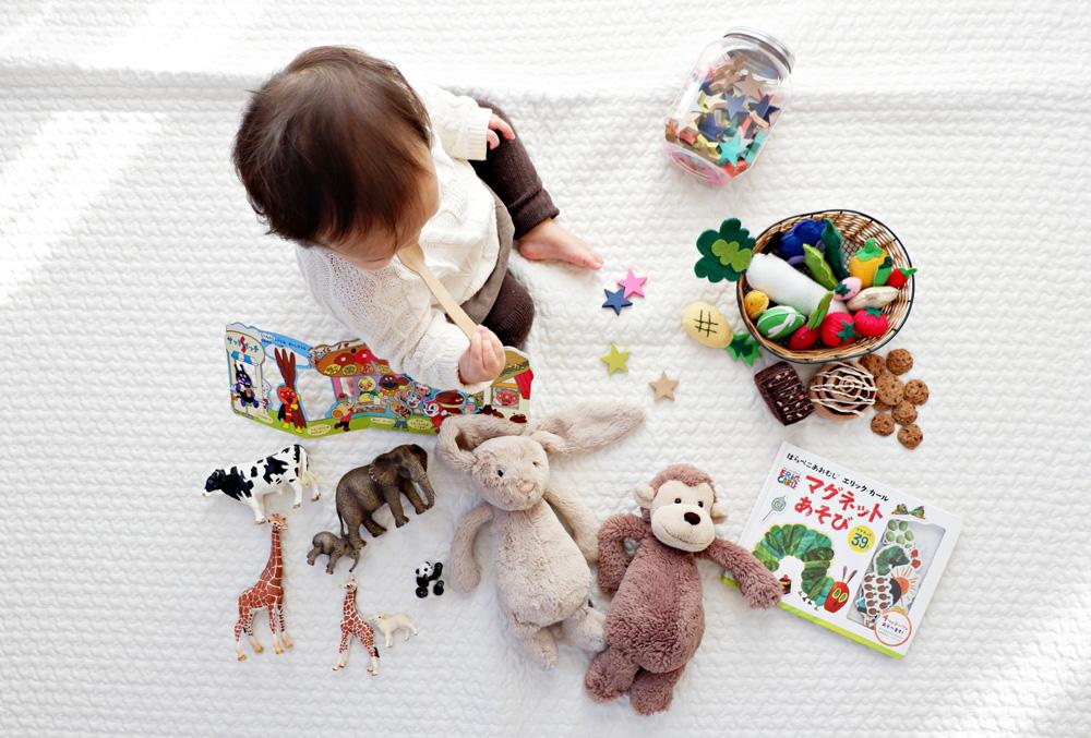 Bebê brincando em um tapete branco com diversos brinquedos espalhados ao seu redor. A imagem ilustra os benefícios do home office após licença maternidade e paternidade