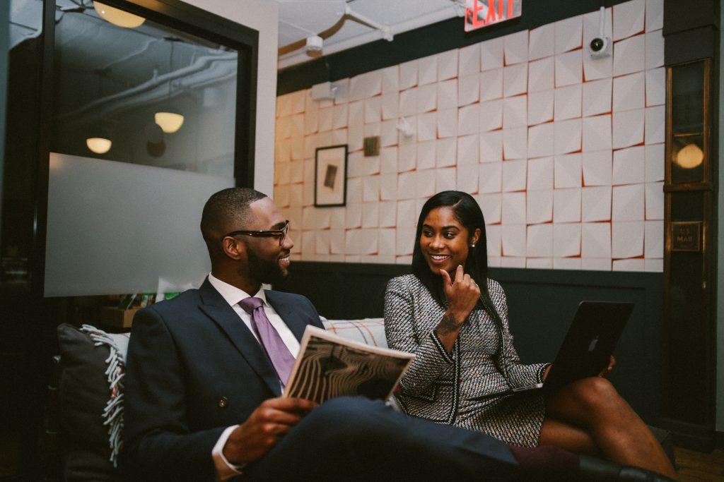 Um homem e uma mulher sentado em uma sala de uso público. Estão formalmente vestidos. Ela com um notebook no colo e ele com um jornal. Uma representação da possibilidade do home office de levar o seu trabalho para qualquer lugar que seja necessário.