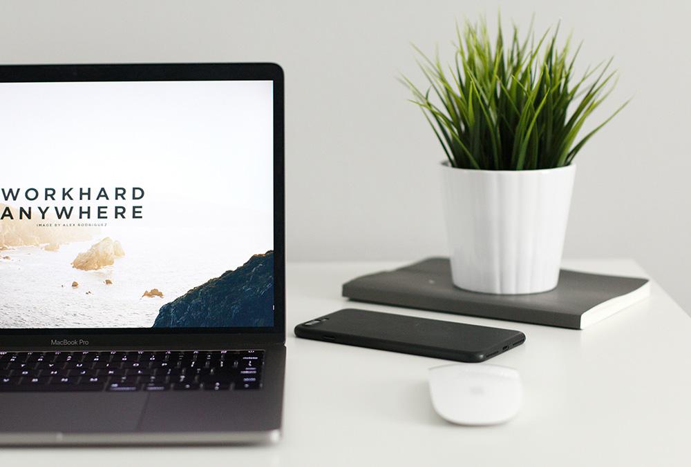 """Notebook, vasinho com planta de mesa, mouse e celular sobre mesa branca. O papel de parede do notebook diz """"workhard anywhere"""". A imagem ilustra o texto """"home office na advocacia: 9 princípios ADVBOX""""."""