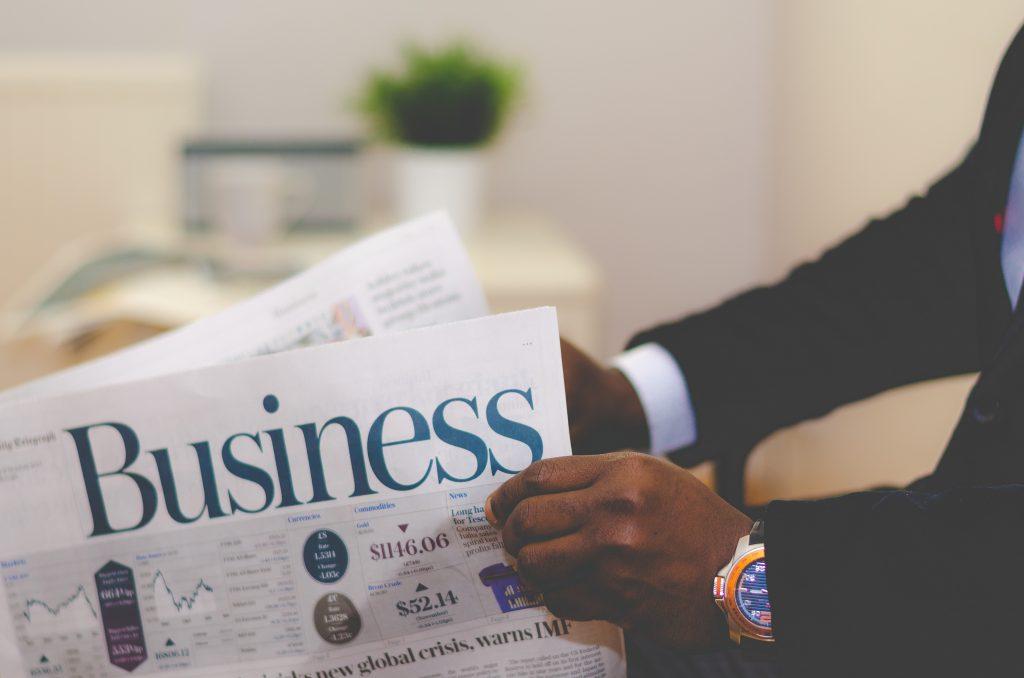 Homem de terno folheando um jornal de economia, mostrando a impostância de bsucar informação para Não Pagar Imposto Excessivo