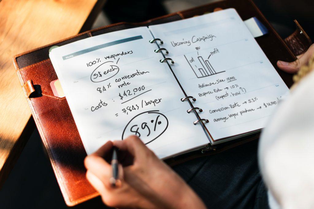 Uma pessoa anotando dados e números em um bolocco de notas, representando o planejamento em marketing jurídico