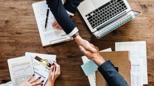 Advogados apertando mãos sobre uma mesa com diversas planilhas e um computador, simbolizando o Marketing Jurídico Digital