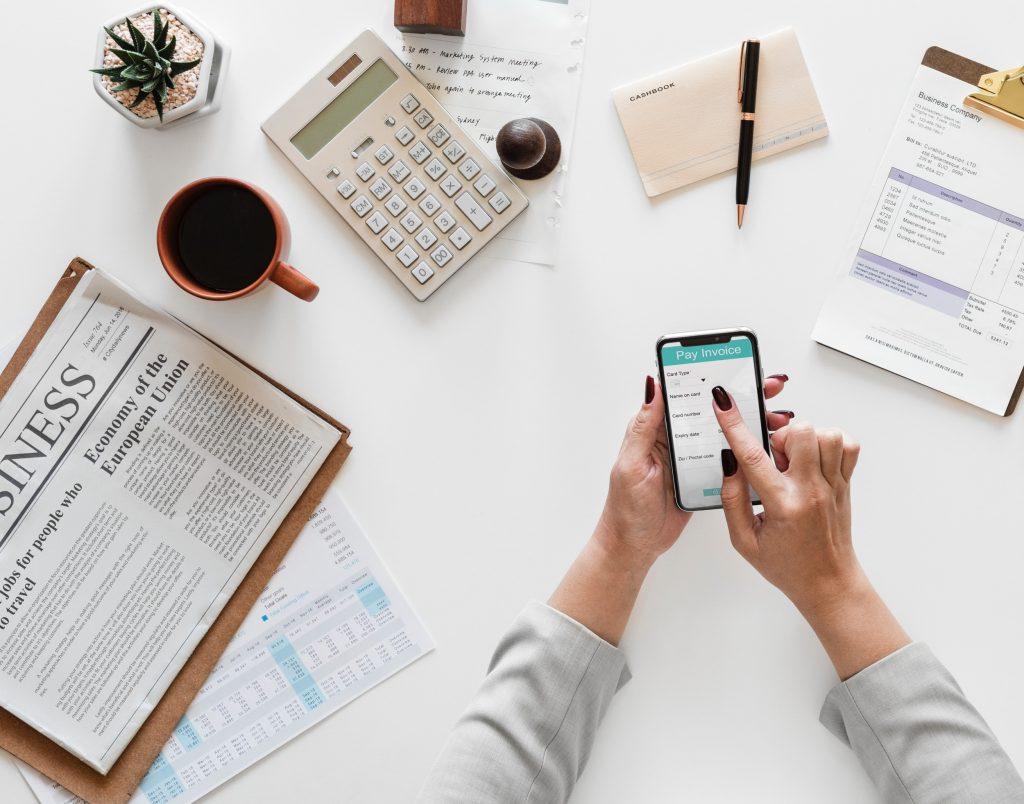 Uma mão manuseando um smartphone sobre uma mesa. na mesa estão uma xícara de café, um jornal, uma calculadorae algumas planinhas de planejamento. A imagem representa os pontos ee relevar ao criar uma Sociedade Simples de Advogados