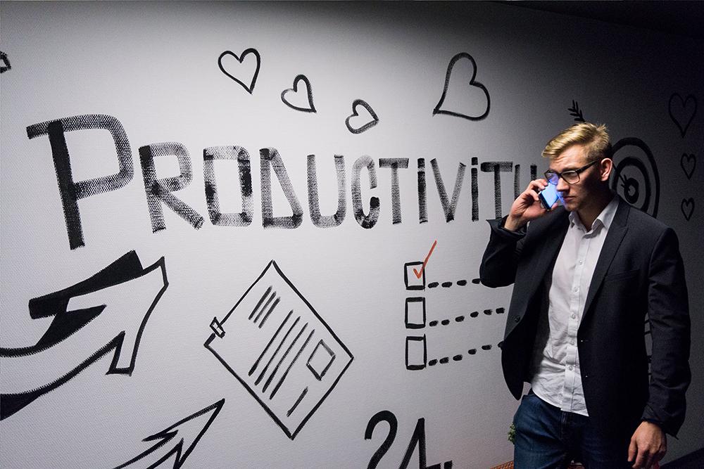 Homem de terno, usando óculos, falando ao celular ao lado de uma parede branca ccom desenhos em preto que fazem referência a planejamento e cumprimento de metas. Foto simboliza características de um advogado gestor