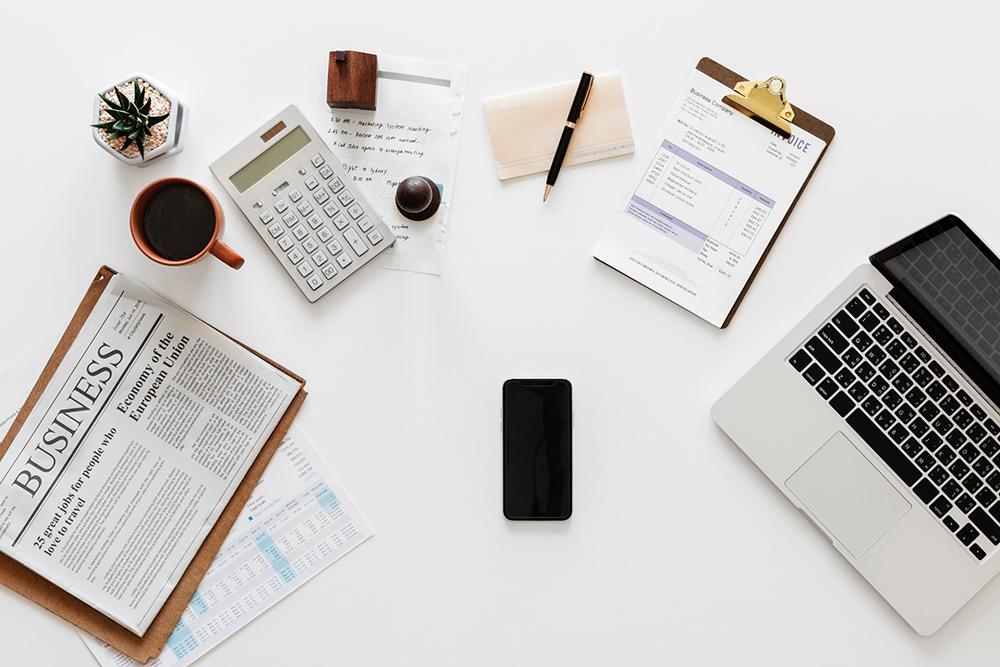 Uma mesa branca com diversas coisas em cima: notebook, celular, planilhas, calculadora, bloco de anotações e caneta. Representa o planejamento financeiro para a implementação do marketing jurídico