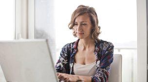 Uma mulher sentada à uma mesa trabalhando em um notebook sem nenhum papel por perto, exemplificando as vantagens da digitalização de documentos