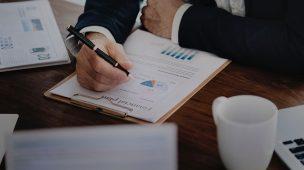 Homem deterno debruçado sobre uma mesa fazendo anotações com uma caneta em um papel contendo gráficos. Sobre a mesa, um teclado de computador e uma xícara de café. Imagem representa os cuidados financeiros a serem tomados em prol do sucesso do seu escritório