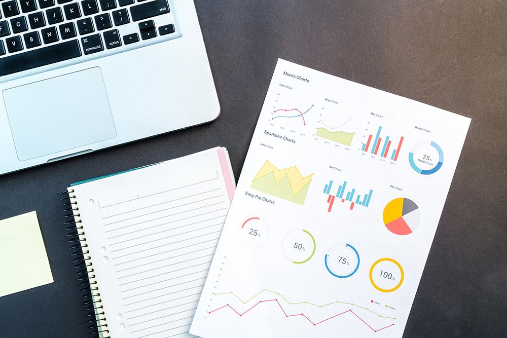Gráficos, caderno e notebook sobre uma mesa preta, representando análise de investimentos em marketing jurídico