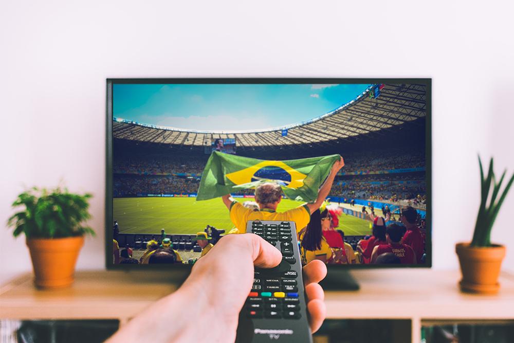 Uma mão apontando o controle remoto para a televisão. Na tela, um torcedor com a camiseta do Brasil no estádio levantando uma bandeira da seleção. Foto ilustra dicas para ter tempo de assistir aos jogos sem prejudicar a produtividade do seu trabalho.
