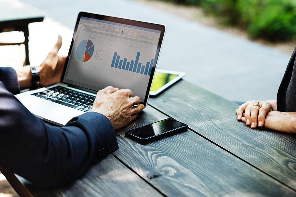 Um advogado analisando um gráfico na tela de um notebook, demonstrando a importância da análise financeira