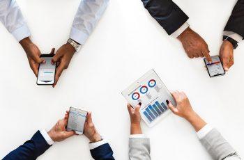 Afoto é uma visão de cima de uma mesa branca onde quatro pessoas (que só aparecem os braços) estão mexendo em celulares e tablets, analisando diferentes tipos de gráficos. Representa a análise de dados necessária na advocacia digital.