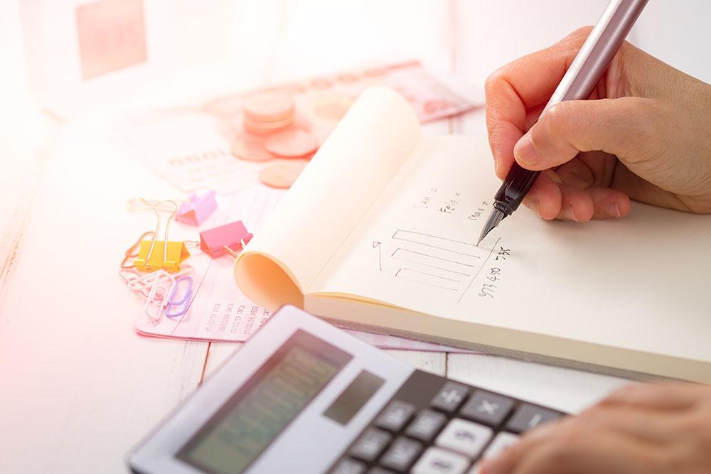 Uma pessoa anotando em um bloco de notas com uma calculadora ao lado. Imagem representa o cuidado com os custos do escritório