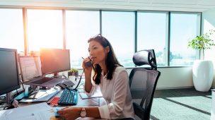Uma mulher falando ao telefone em um escritório com vista panorâmica. Em sua mesa, diversos gráficos com dados sobre atendimento. Representa a importância do CRM no marketing jurídico.