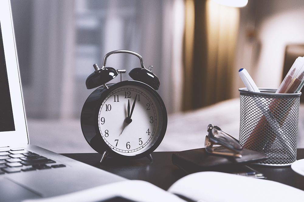 Um relógio sobre uma mesa de trabalho com livros e computador, representando quanto tempo demora um processo