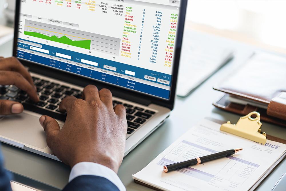 Homem digitando em um computador onde a tela exibe diversos gráficos financeiros, representando os cuidados com as finanças em um Escritório digital