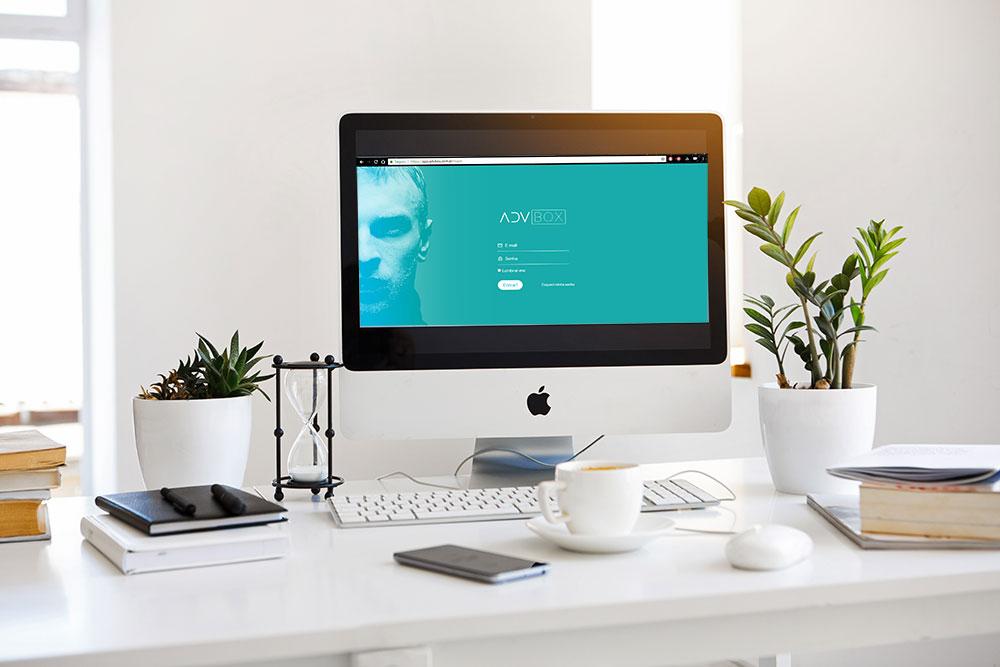 Imagem mostra uma mesa com um computador em cima. Na tela do computador está sendo exibida a página de login da ADVBOX, ferramenta de gestão e produtividade para escritórios de advocacia.
