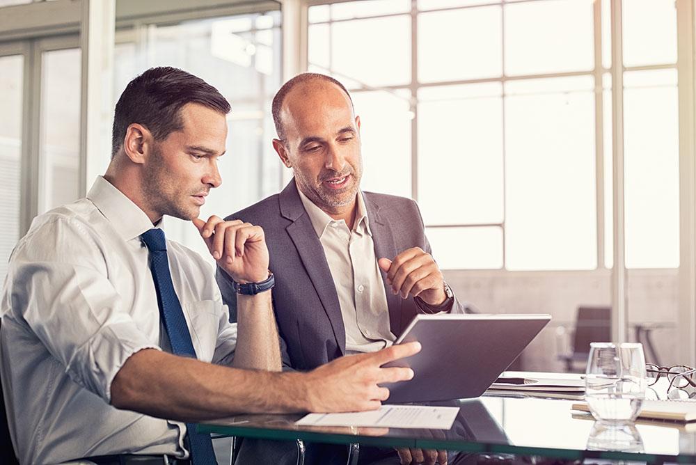 Um advogado mostrando para outro alguns dados em um tablet, prática comum no marketing jurídico