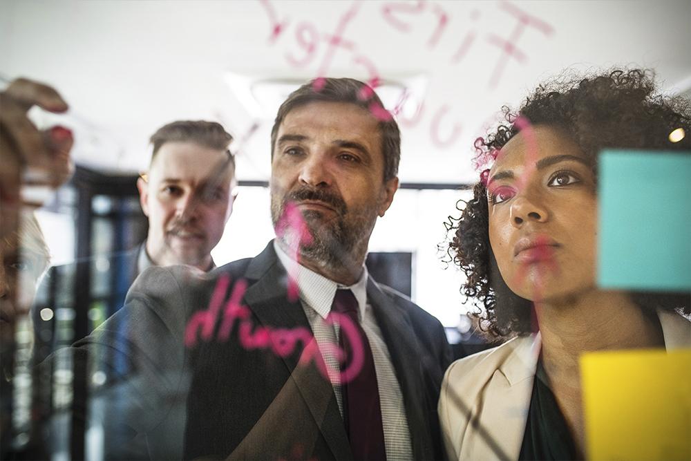 Homem escrevendo informações em um painel de vidro, sendo assistindo por uma mulher e outro homem. Foto representa a Organização do escritório