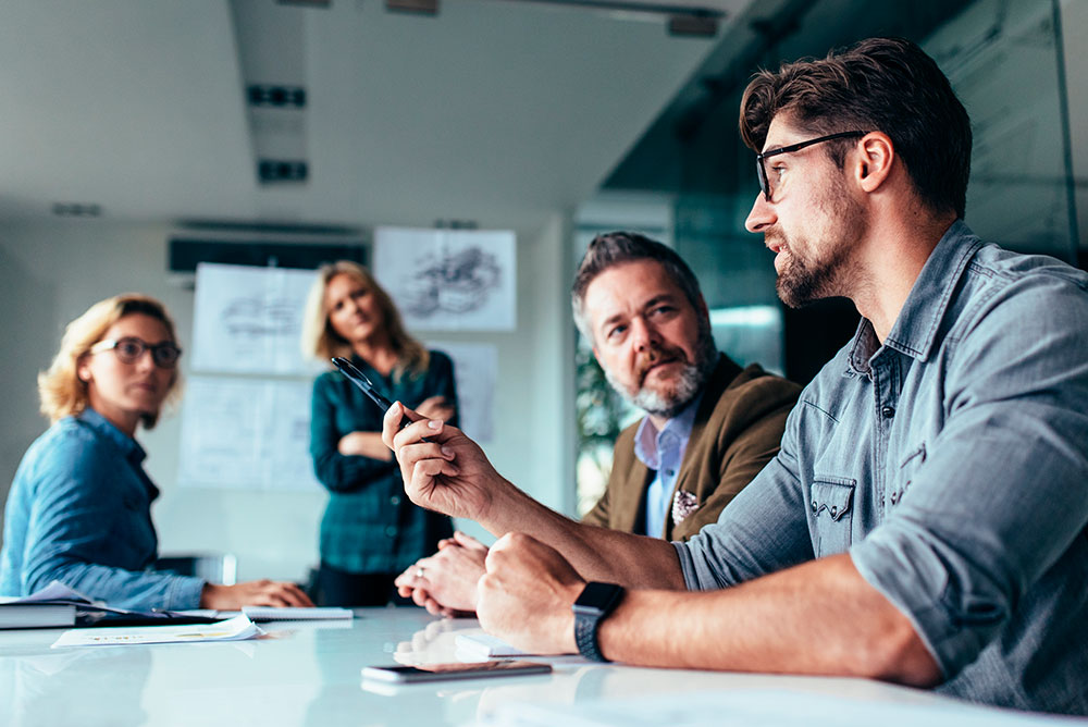 Um homem explicando para outros membros da equipe em uma sala de reunião sobre estratégias de Atendimento jurídico
