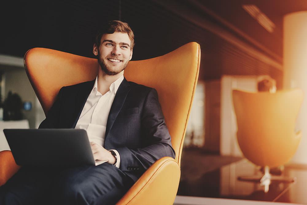 Jovem advogado sentado em uma poltrona sorrindo com um notebook sobre o colo e olhando por uma janela. Imagem tenta ilustrar a persona do Advogado empreendedor