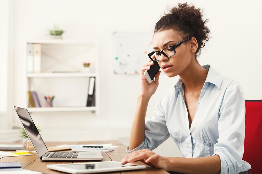 Uma advogada realizando Atendimento Jurídico pelo telefone enquanto usa, também, um tablet