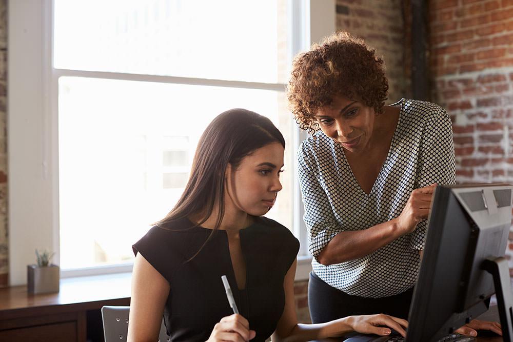 Duas mulheres olhando para uma tela de computador em um escritório e aprendendo a usar um Software jurídico