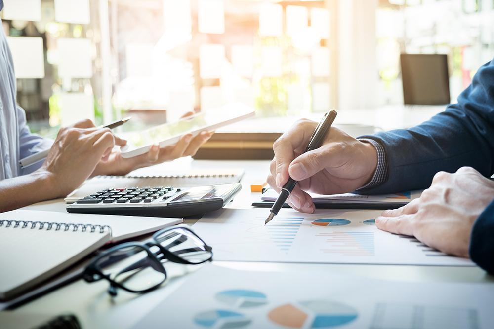 Duas pessoas frente à frete em uma mesa. A mulher manipula uma calculadora enquanto o homem faz anotações sobre diversas folhas com gráficos., representando os cuidados com a Gestão financeira de escritórios de advocacia