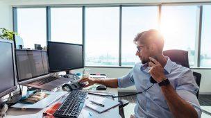 Um homem usando o telefone enquanto mexe em um computador em um escritório de advocacia com vista panorâmica. Foto está relacionada com Atendimento jurídico