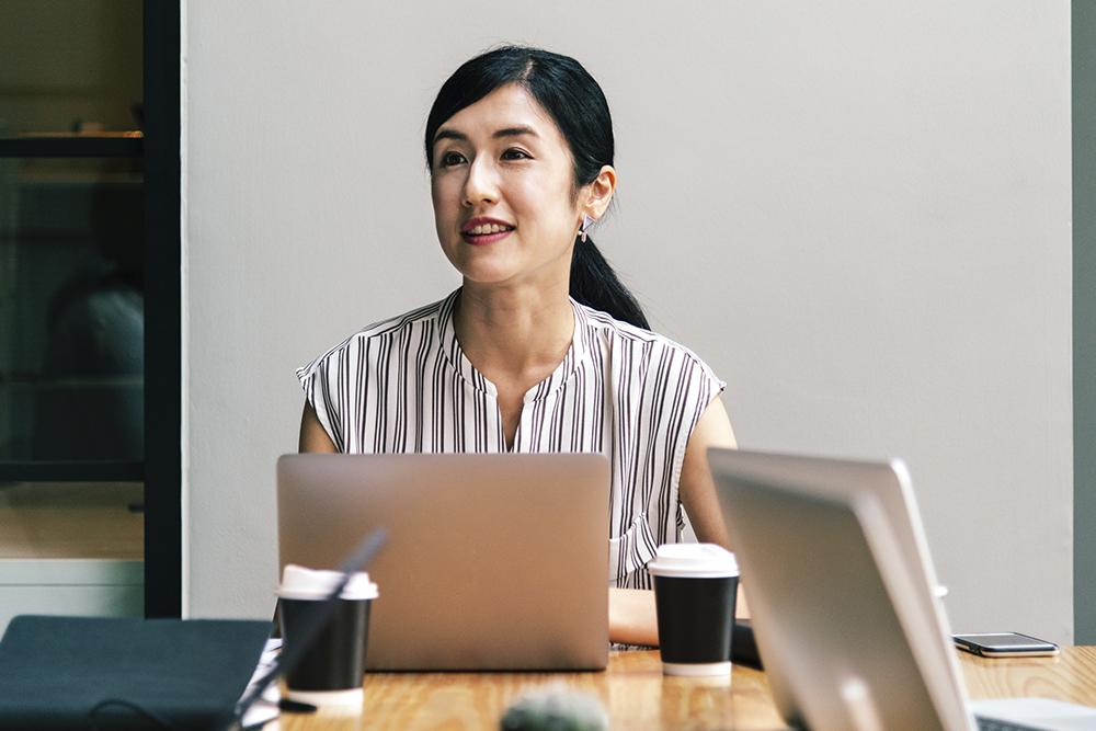 Uma mulher sorridente trabalhando em uma mesa sobre onde está um notebook. Representa a qualidade do serviço à distância de um Advogado online