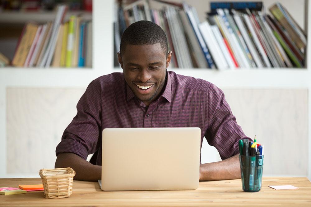 Um homem sorrindo em frente a um notebook sobre uma mesa, demonstrando as facilidades de um atendimento jurídico otimizado