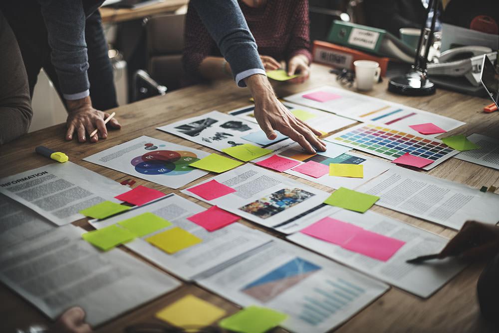 Vários documentos e planilhas sobre uma mesa com post-its coloridos colados, demonstrando a organização do fluxo de trabalho na advocacia