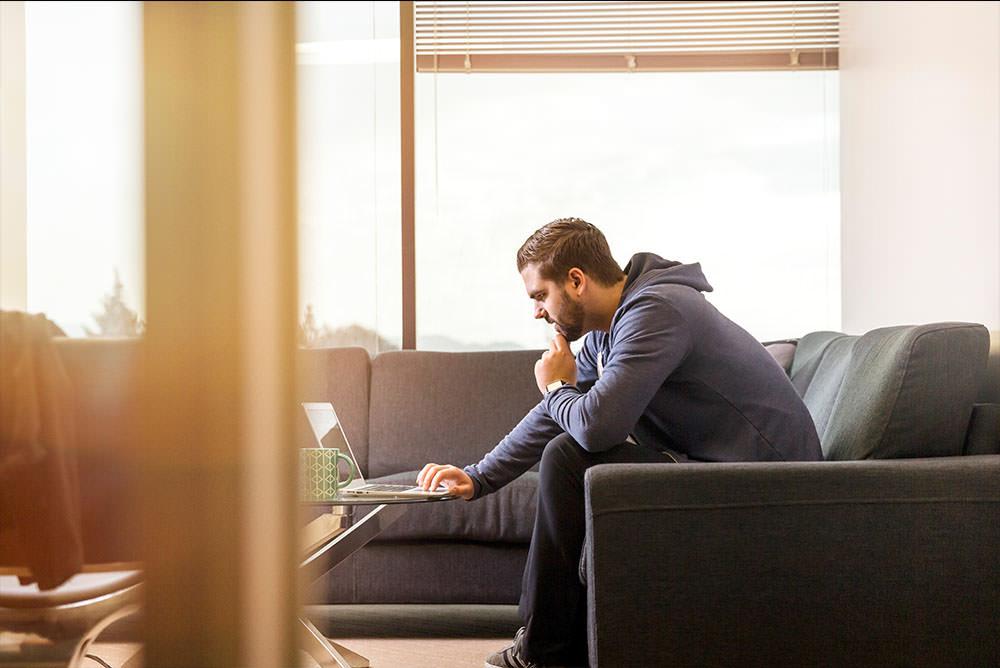 Advogado em casa com roupas informais mexendo no notebook. Representa a possibilidade de realizar a Gestão de escritório de advocacia à distância e com qualidade.