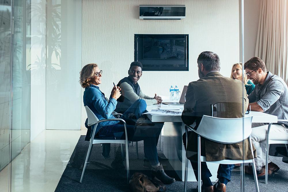 Diversas pessoas ao redor de uma mesa em uma sala de reunião sorrindo. Imagem ilustra satisfação do escritório digital.