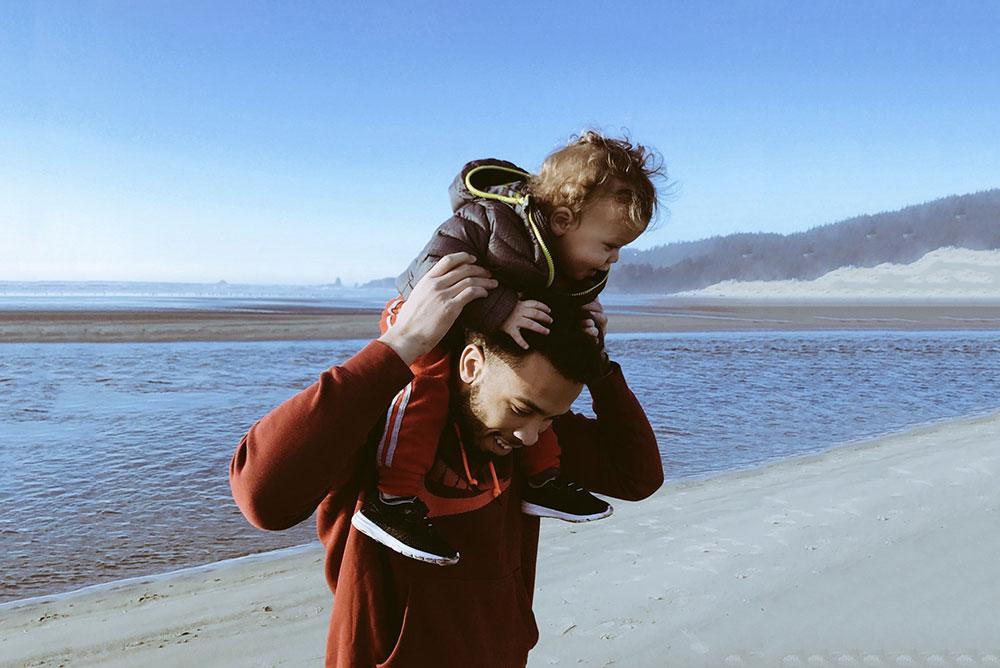 Um pai carregando o filho nas costas em uma praia, representando a celebração do Dia dos Pais.