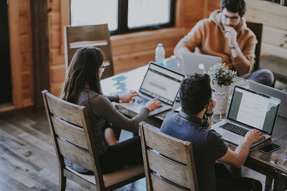 Três pessoas sentadas junto a uma mesa trabalhando em notebooks que mostram na tela softwaresde gestão, representando a gestão de escritórios de advocacia